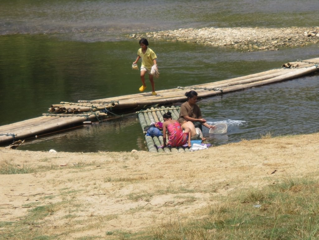 People doing laundry in the river at the elephant camp