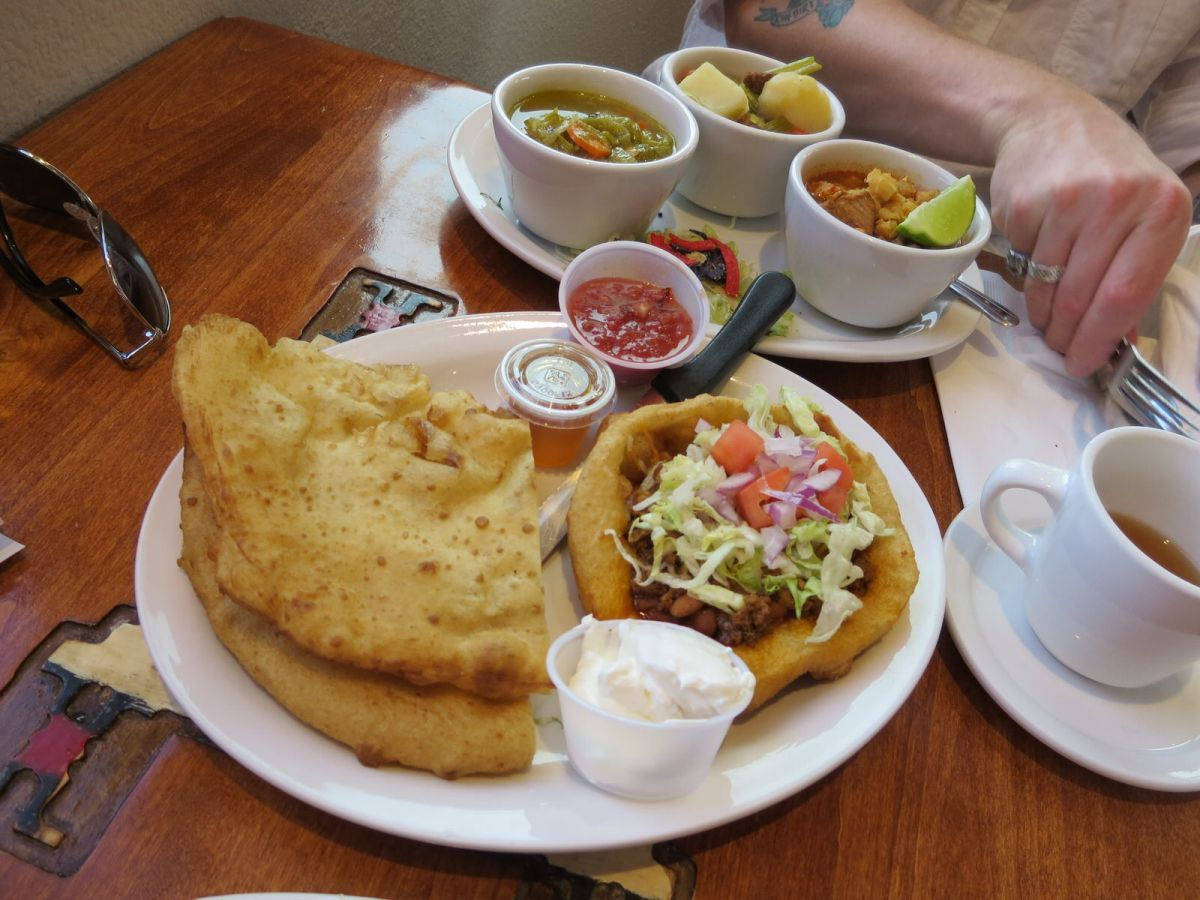The Navajo sampler platter: Green Chili Stew, Red Chili Pork Posole, Sheep Camp Mutton Stew, mini Navajo Taco, and Navajo fry bread with honey