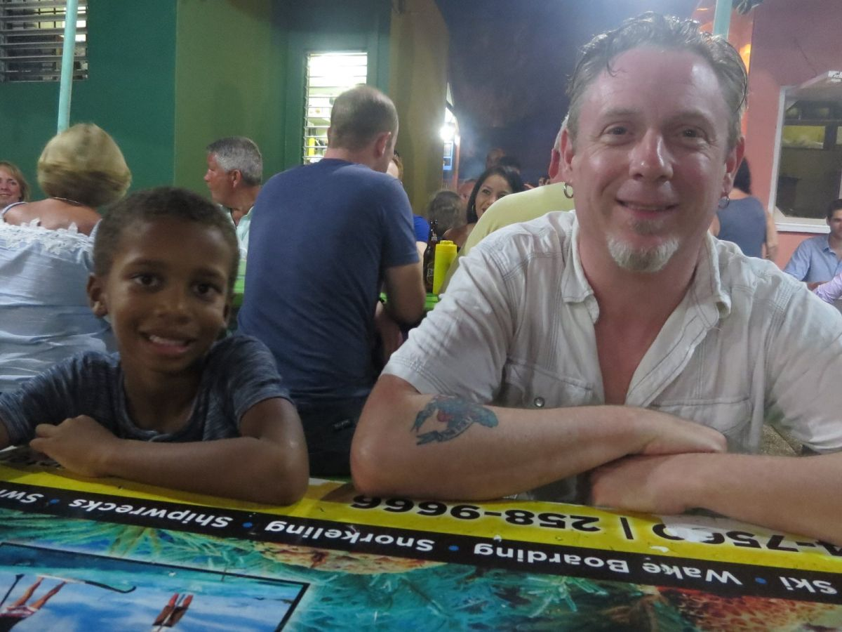 Dimitri and Paddy holding the table at Oistins Fish Fry, Barbados